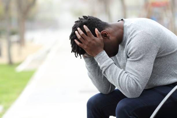trauriger depressiver schwarzer mann auf einer bank in einem park - verzweiflung stock-fotos und bilder
