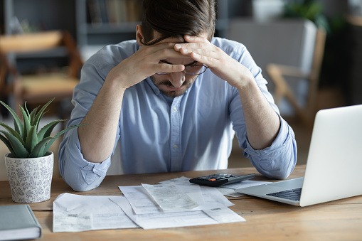 Sad depressed man checking bills, anxiety about debt or bankruptcy, financial problem, bank debt or lack of money, unhappy frustrated young male sitting at work desk with laptop and calculator