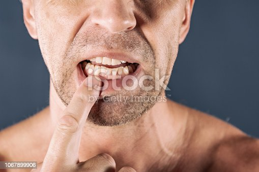 Sad depressed man in pain holding his gum. Portrait of a man on blue background.