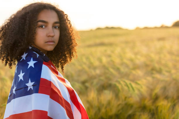 Sad depressed mixed race African American girl teenager female young woman with tears in her eyes in a field of wheat or barley crops holding and wrapped in USA stars and stripes flag in golden sunset evening sunshine stock photo