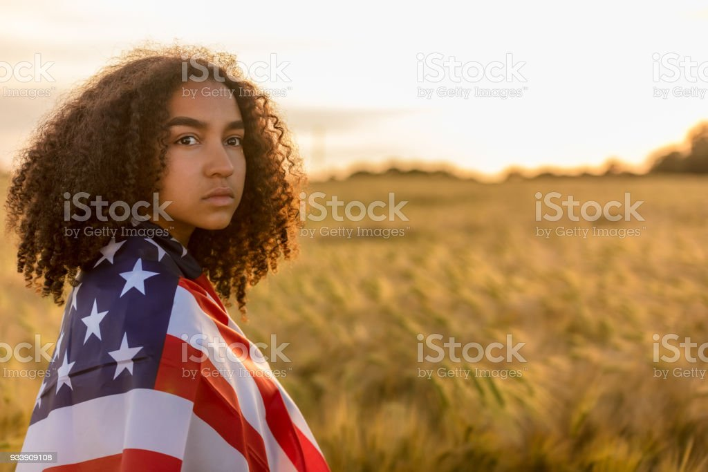 Sad depressed mixed race African American girl teenager female young woman in a field of wheat or barley crops wrapped in USA stars and stripes flag in golden sunset evening sunshine stock photo