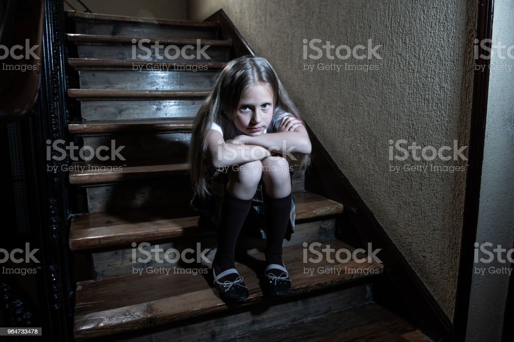 Sad, depressed, unhappy schoolgirl suffering from bullying feeling lonely and hopeless sitting on stairs with dark light. royalty-free stock photo