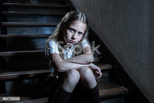 istock Sad, depressed, unhappy schoolgirl suffering from bullying feeling lonely and hopeless sitting on stairs with dark light. 964733538