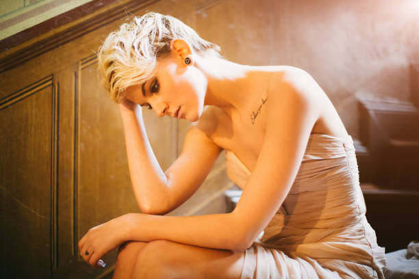 Sad depressed young woman in evening gown sitting on wooden stairway stock photo