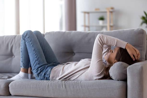 sad deprimerad ung kvinna liggande på soffan känsla huvudvärk - kronisk sjukdom bildbanksfoton och bilder