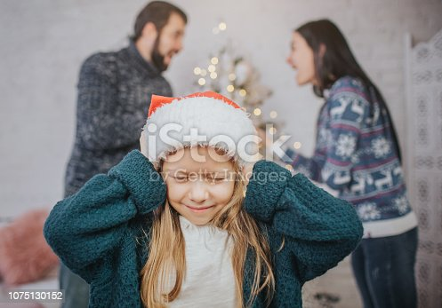 istock Sad, desperate little girl during parents quarrel. Clog the ears.. Family quarrel on the eve of Christmas. 1075130152