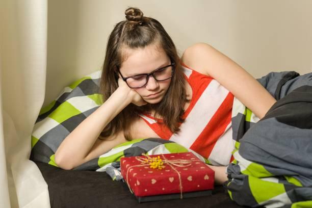 traurig enttäuscht teen mädchen sitzen im bett zu hause geschenk betrachten - jugendliche geburtstag geschenke stock-fotos und bilder