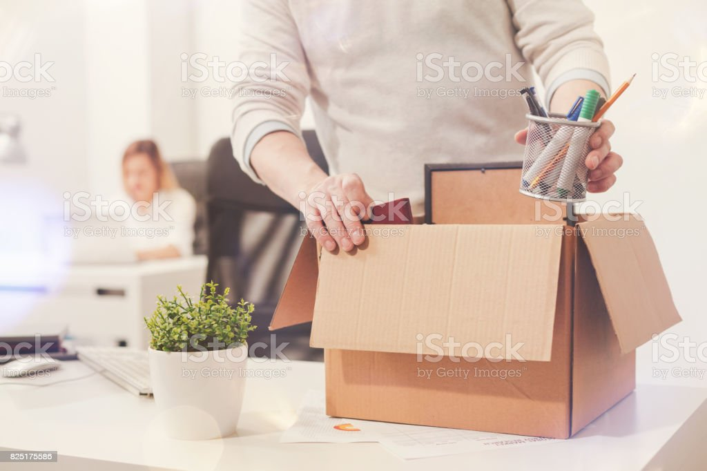 Sad dismissed worker taking his office supplies with him stock photo