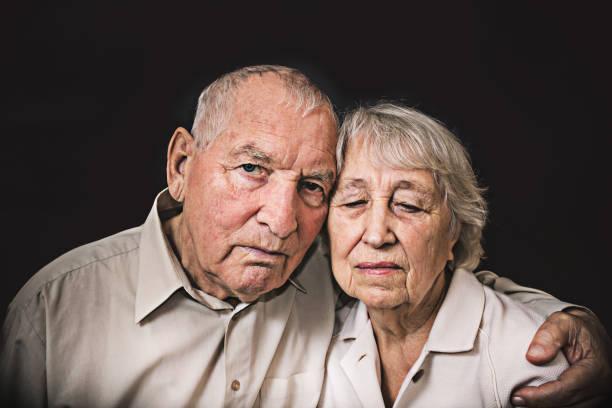 Trauriges älteres Paar auf schwarzem Hintergrund – Foto