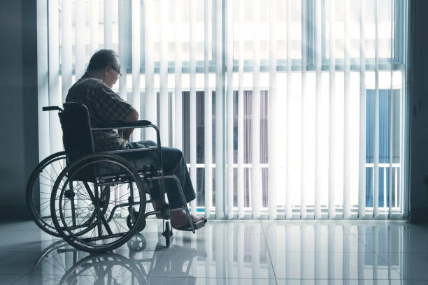 Sad elderly man sits in the wheelchair stock photo