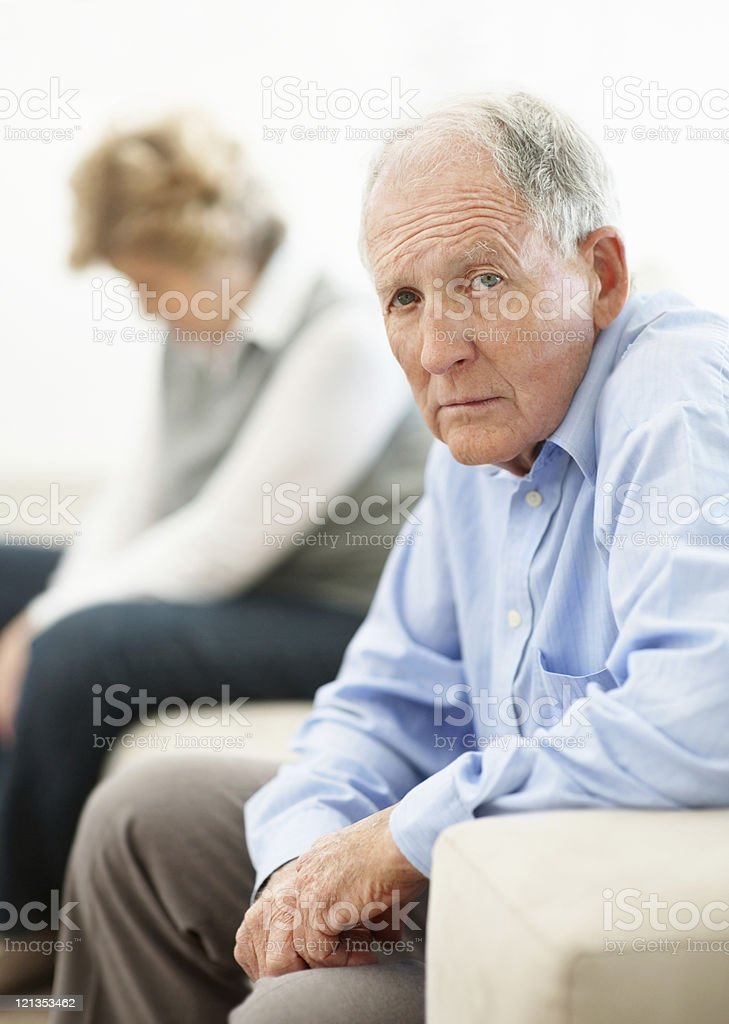 Sad elderly man sitting on sofa with woman royalty-free stock photo