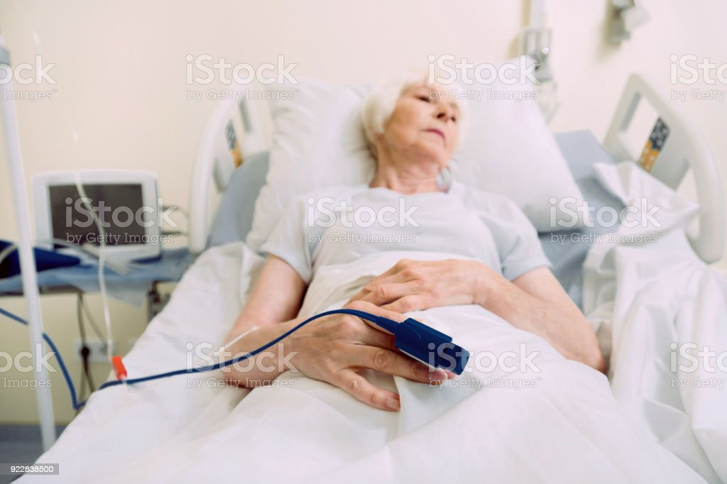 Sad Elderly Woman With Heart Rate Medical Equipment At Hospital Stock Photo  - Download Image Now