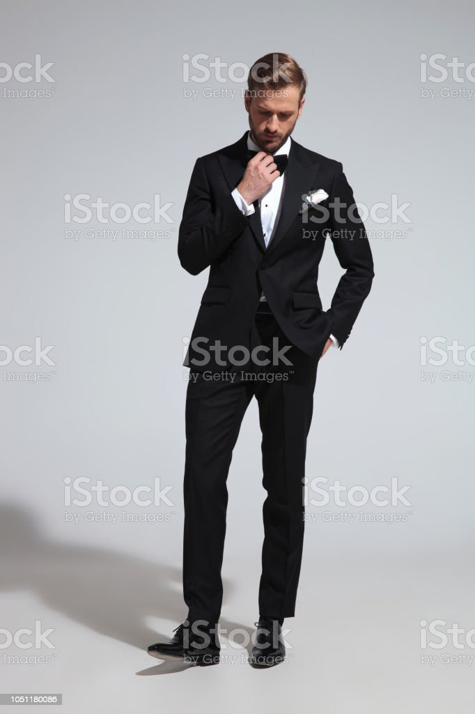 4f0f37507bdd sad elegant man looks down while fixing bowtie royalty-free stock photo