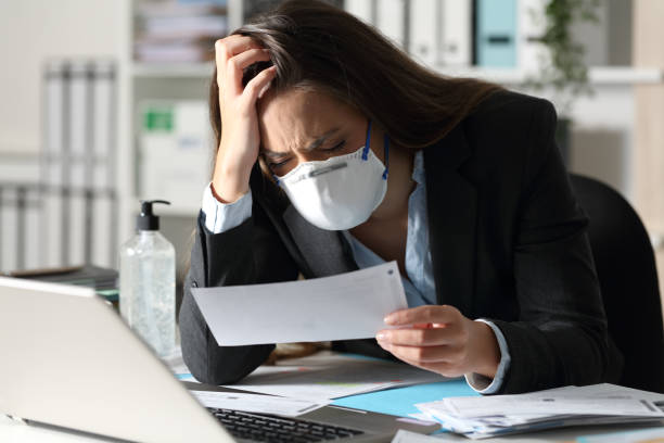 Sad executive with mask complaining looking receipt stock photo