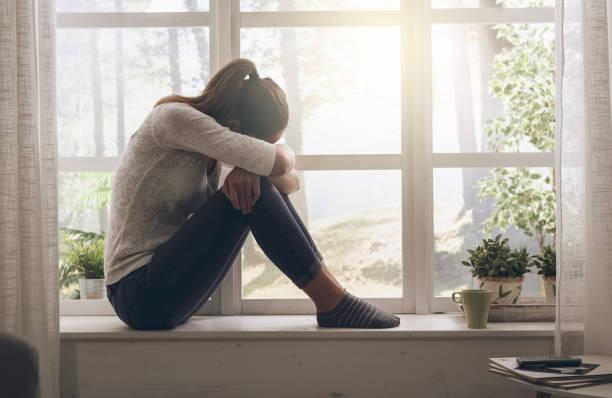 Sad esgotado a mulher sentada ao lado da janela, ela é solitário e cansado - foto de acervo