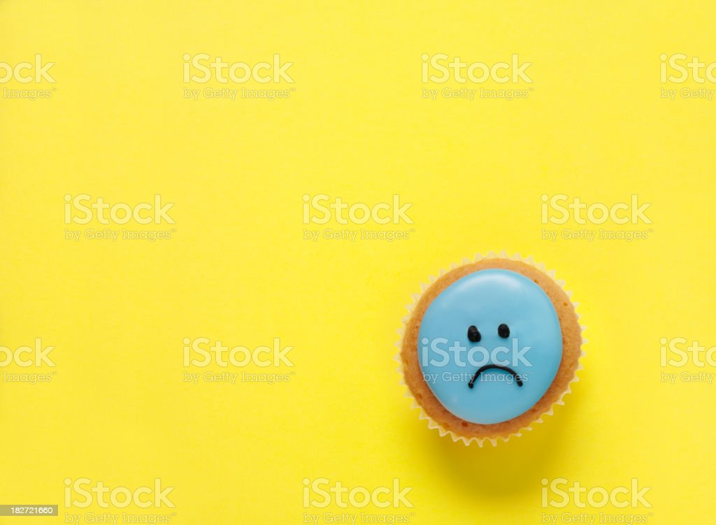 Sad Face Cupcake on a Yellow Background royalty-free stock photo
