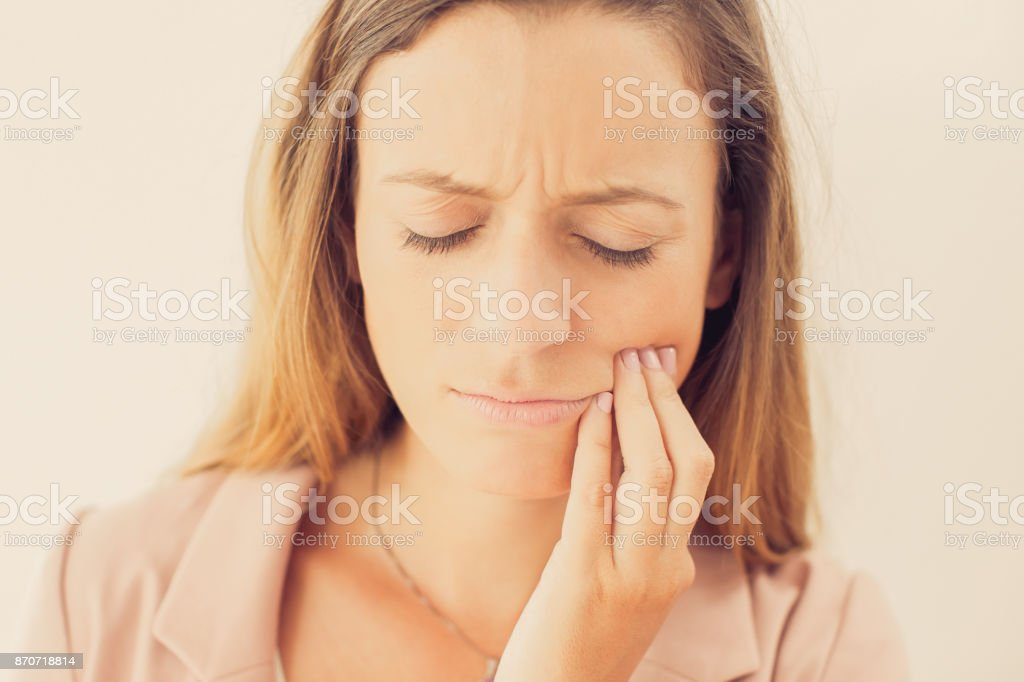 Sad face of young businesswoman having toothache stock photo