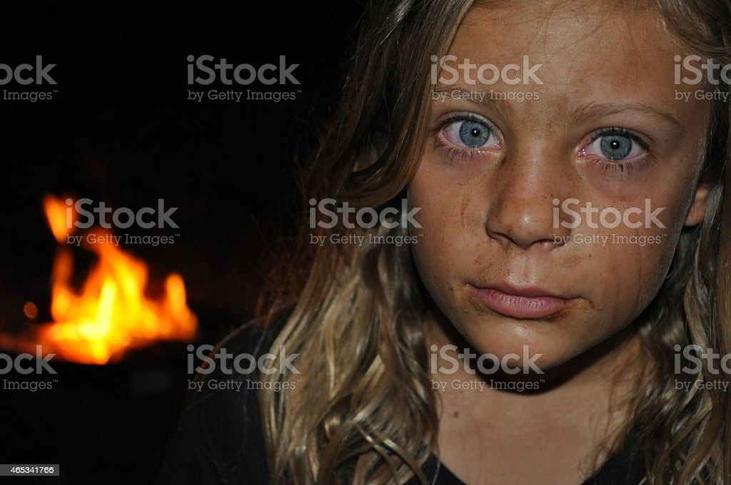 A young girl with vibrant blue eyes sitting around a campfire.