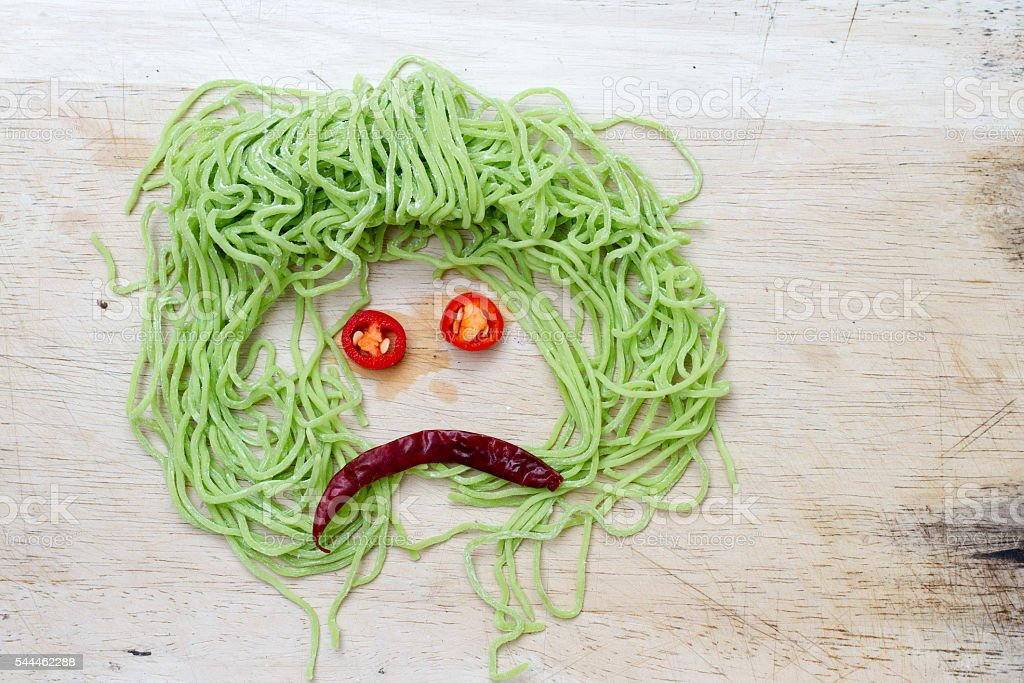 sad faces on wood background made from vegetable and noodle stock photo