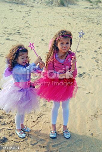 Two young girls dressed as fairies complet with wands stand crying and sad on a beach.