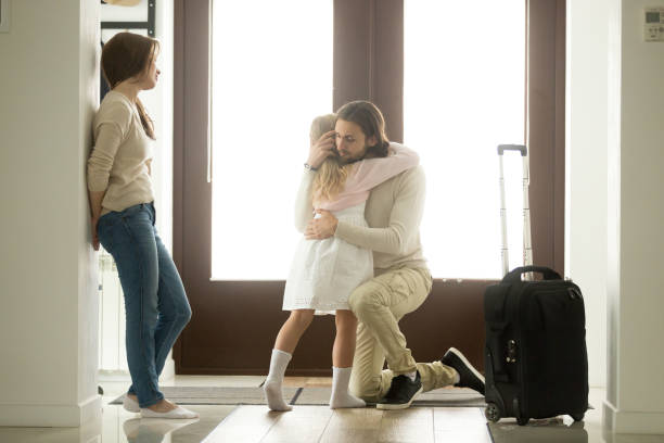 sad father hugging little daughter before leaving for long trip - separation stock photos and pictures