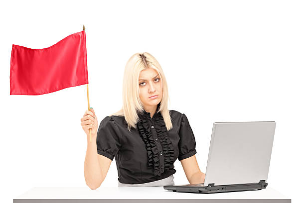 traurig weibliche büroangestellter winkt eine rote flagge - rot bekümmerte möbel stock-fotos und bilder