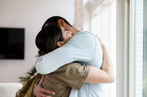 Sad mid adult  female soldier hugs her husband goodbye as she leaves for military duty.