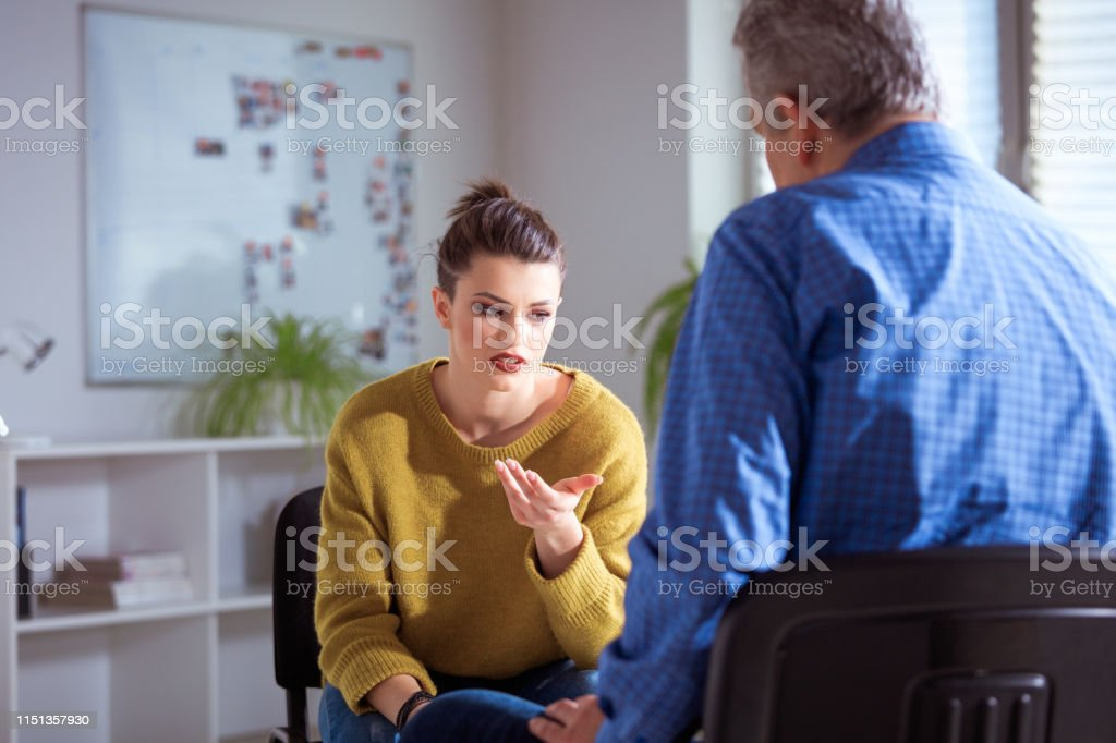 Sad female student sharing problems to therapist Sad university student gesturing while sharing problems to therapist. Mature mental health professional is having meeting with young woman. They are sitting in lecture hall. 18-19 Years Stock Photo