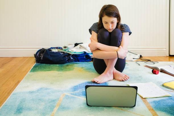 Traurige weibliche Teenager beobachten Medien auf Laptop umarmt sich – Foto