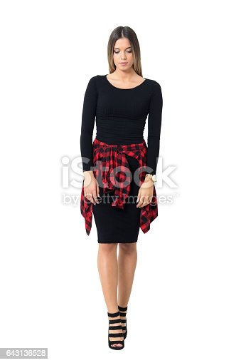 Sad young feminine woman in black dress and stiletto walking and looking down. Full body length isolated over white studio background.