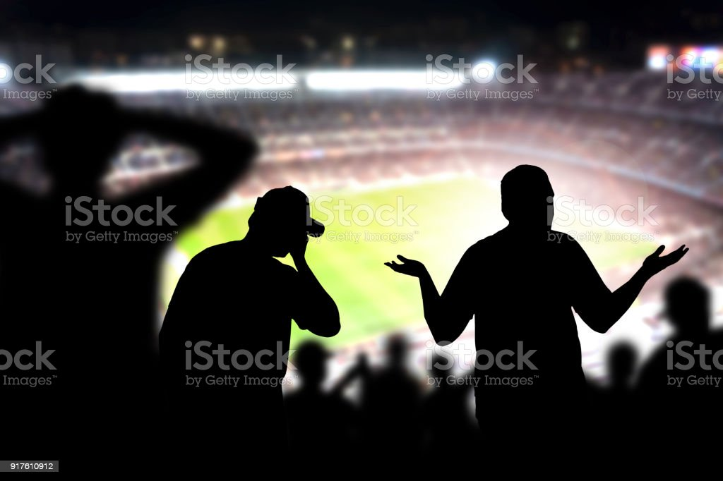Sad football fans. Disappointed, angry and upset crowd in a match in a soccer stadium. Favourite team and club lost game. Devastated audience in live sport event. stock photo