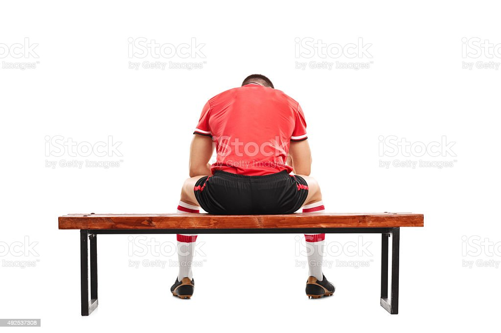 Sad football player sitting on a wooden bench stock photo