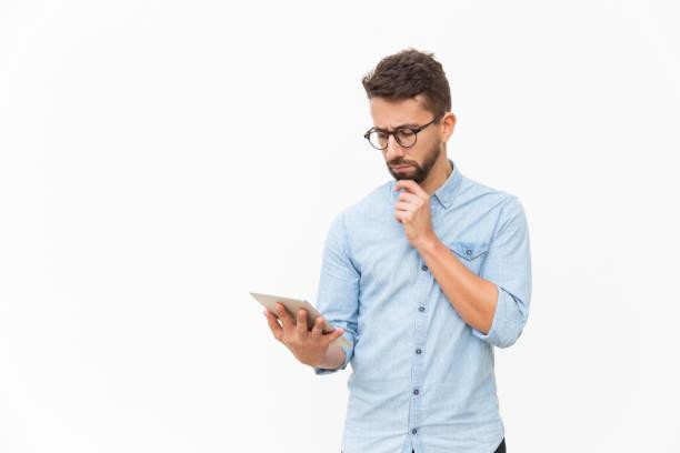 Trauriger Stirnrunzeln Kerl mit Tablet-Leseinhalt – Foto