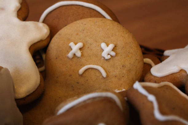 Sad gingerbread man in the woven basket Homemade gingerbread men in the woven basket on the wooden table. Depressed christmas cookie with sad face covered with icing. New Year pastry in the shape of stars and men. Winter background sugar cane stock pictures, royalty-free photos & images