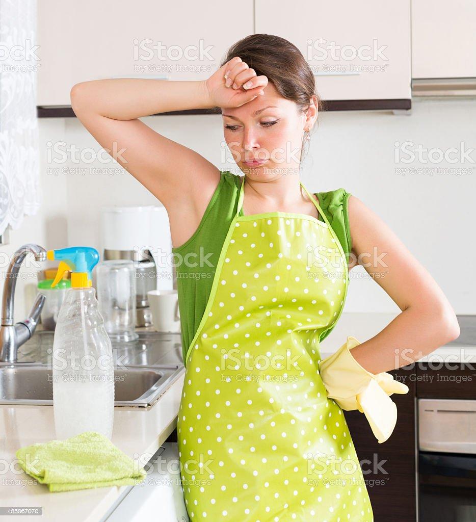 Sad girl cleaning furniture stock photo
