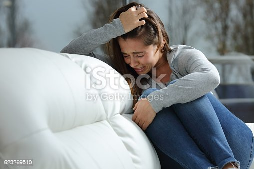 istock Sad girl crying alone at home 623269510