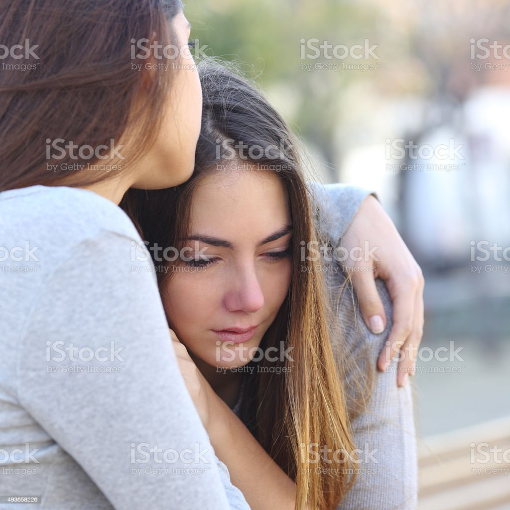 Sad girl crying and a friend comforting her stock photo