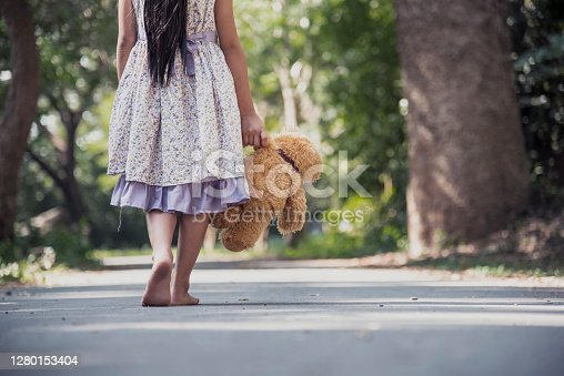 Sad girl hugging teddy bear sadness alone in green garden park. Lonely girl feeling sad unhappy walking outdoors with best friend toy. Autism child play teddy bear best friend. Family violence concept