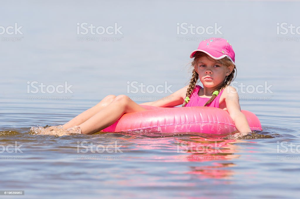 Sad girl in cap floating river sat on swimming circle stock photo