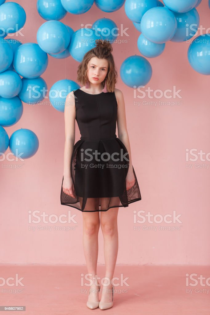 265cc06b5b0c Sad girl in cute black dress on pink background. Indoor portrait of  blissful european young woman with blue ballons hanging - Stock image .