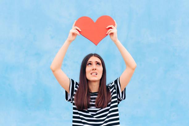 Traurige Mädchen in Liebe halten großes rotes Herz – Foto
