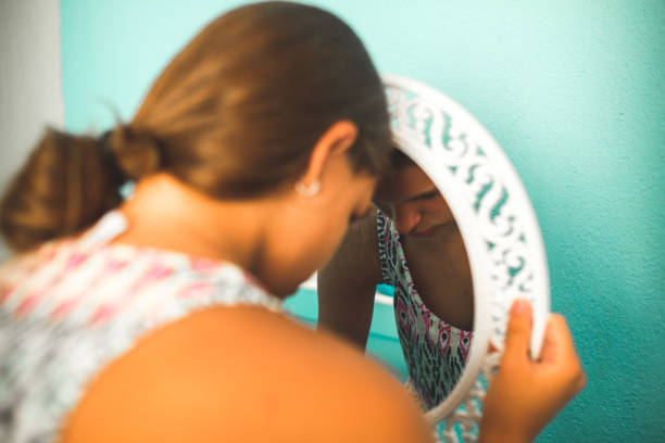 Sad girl in the mirror Sad girl in the mirror low self esteem stock pictures, royalty-free photos & images