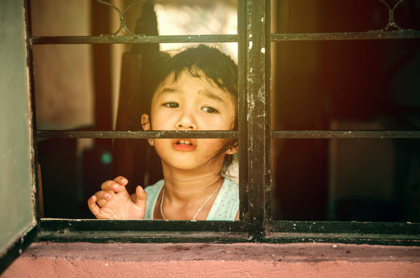 sad girl in the window - philippines girl stock photos and pictures
