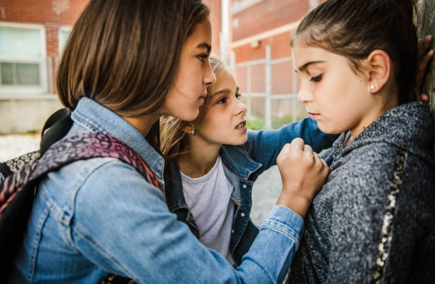 A sad girl intimidation moment on the elementary Age Bullying in Schoolyard stock photo
