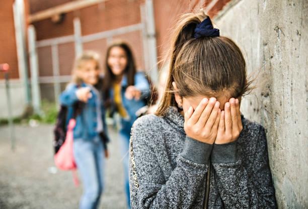 Ein trauriges Mädchen Einschüchterung Moment auf der Grundschule Alter Mobbing in Schoolyard – Foto