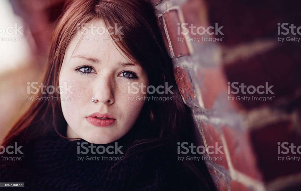 Sad girl is leaning against the wall stock photo