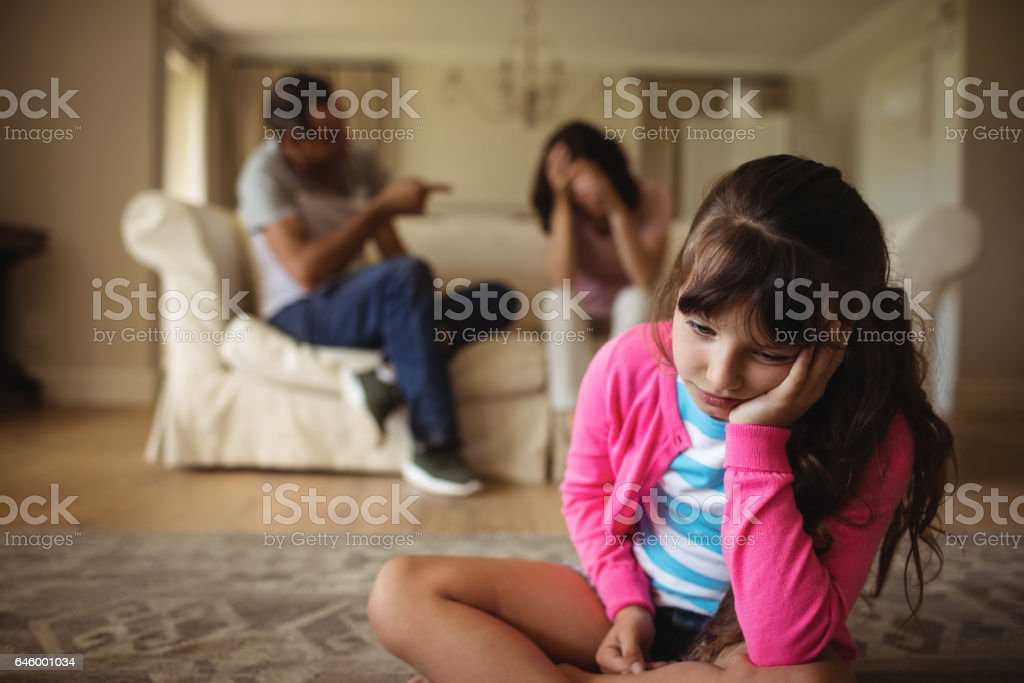 Sad girl listening to her parents arguing stock photo