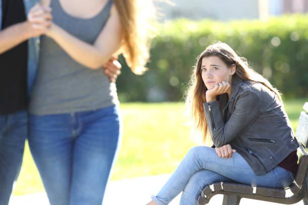 カップル歩いて見て悲しい少女 - 羨望 ストックフォトと画像
