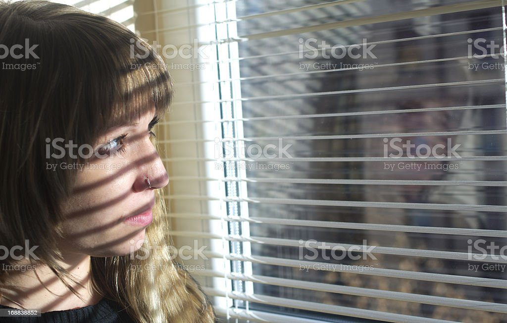 Portrait of the beautiful girl looking through window