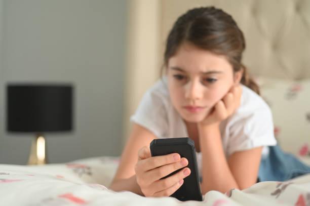 Sad girl reading a bullying post on social media stock photo